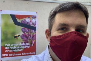 """Jens Matheuszik vor dem Plakat """"Wir unterstützen die Volksinitiative Artenvielfalt"""" (SPD Bochum-Ehrenfeld)"""